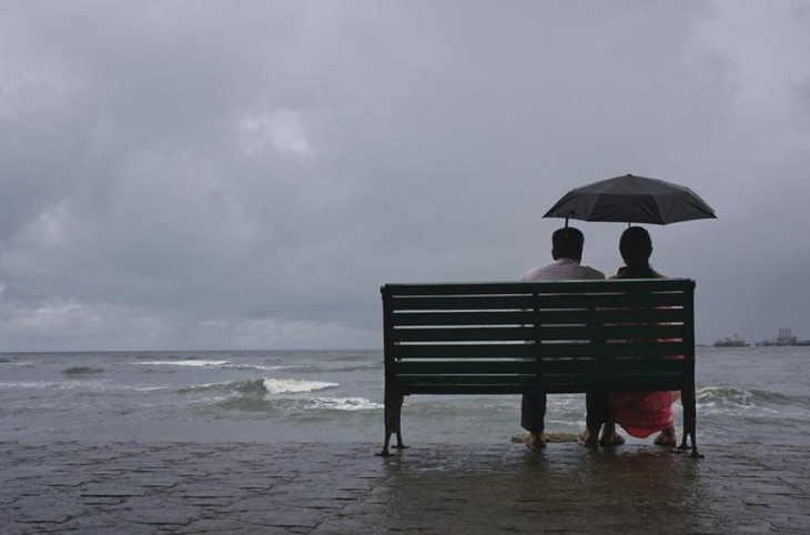 A couple rests on a seaside promenade during a rain shower in Kochi