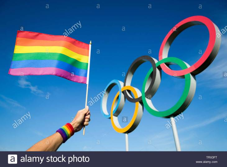 london-may-4-2019-a-hand-wearing-rainbow-colored-sweatband-waves-a-gay-pride-flag-hangs-in-front-of-olympic-rings-against-bright-blue-sky-TRX3FT